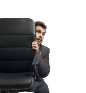 Businessman afraid and hiding behind a chair